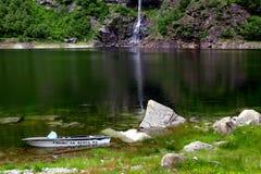 Opinião do lago com barco e cachoeira em Itália, Domodossola Foto de Stock Royalty Free