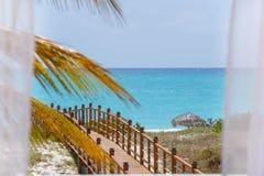 Opinião do mar através das cortinas brancas na praia Fotos de Stock Royalty Free