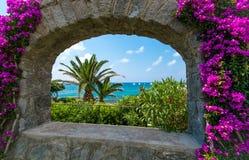 Opinião do mar através do arco quadro pela buganvília foto de stock royalty free