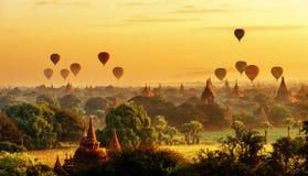 Opinião do nascer do sol de pagodes bonitos e de balões de ar quente, Myanmar Foto de Stock