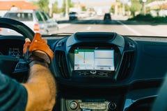 Opinião do painel e mapa de GPS do carro moderno com mãos do motorista On Steering Wheel fotografia de stock