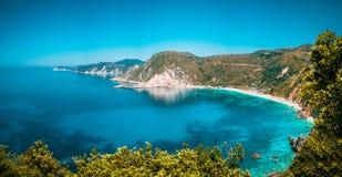Opinião do panorama à praia de Petani com água de mar Mediterrâneo azul transparente e claro na baía pitoresca, ilha de Kefalonia foto de stock