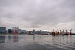 Opinião do panorama do barco do rio, do distrito financeiro e do guindaste no fundo do céu nebuloso imagem de stock