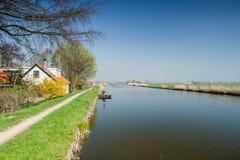 Opinião do panorama com céu azul acima de um po'lder e de uma casa holandeses típicos do dique imagens de stock