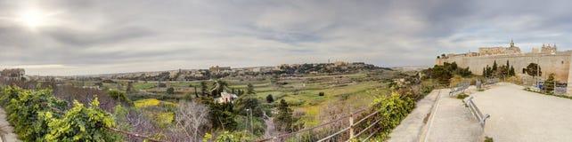 Opinião do panorama de HDR nas paredes históricas velhas de Mdina em Malta com natureza circunvizinha e os céus dinâmicos no temp Imagens de Stock