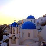 Opinião do por do sol com igreja ortodoxa, Oia, ilha de Santorini, Grécia Fotografia de Stock Royalty Free