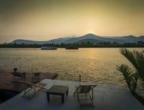 Opinião do por do sol do beira-rio no kampot cambodia Ásia com cadeiras de plataforma Foto de Stock