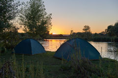 Opinião do por do sol no rio calmo e nas barracas pequenas do turista Fotografia de Stock