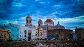 Opinião do por do sol à margem e à catedral de Cadiz, Espanha Imagem de Stock