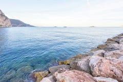 Opinião do por do sol ao mar e às rochas grandes na água Foto de Stock