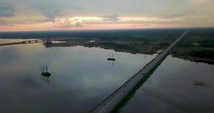 Opinião do por do sol da parte superior do rio com uma ponte video estoque