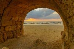 Opinião do por do sol de e arco de Roman Aqueduct, Caesarea fotografia de stock
