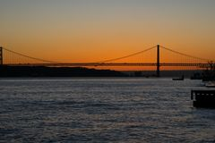 Opinião do por do sol de Tagus River Rio Tajo e 25o de April Bridge Fotos de Stock