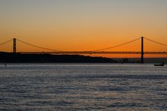 Opinião do por do sol de Tagus River Rio Tajo e 25o de April Bridge Imagens de Stock