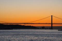 Opinião do por do sol de Tagus River Rio Tajo e 25o de April Bridge Imagem de Stock