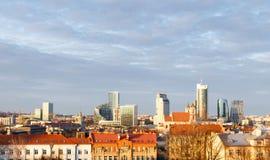 Opinião do por do sol do distrito financeiro do centro em Vilnius, Lituânia Fundo do céu nebuloso e primeiro plano velho da cidad fotografia de stock