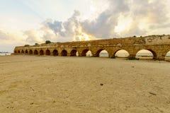 Opinião do por do sol a praia e o Roman Aqueduct em Caesarea imagem de stock royalty free
