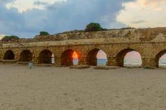 Opinião do por do sol a praia e o Roman Aqueduct em Caesarea fotografia de stock royalty free