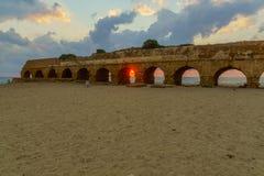 Opinião do por do sol a praia e o Roman Aqueduct em Caesarea imagem de stock