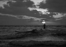 Opinião do por do sol do verão de uma praia sob um céu nebuloso com uma única silhueta do surfista do sup em preto e branco fotos de stock royalty free