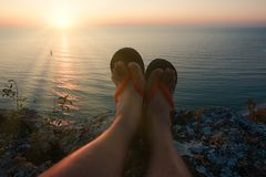 A opinião do POV de equipa os pés nos flip-flops no penhasco alto na frente do sol de ajuste foto de stock