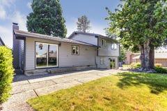 Opinião do quintal de uma grande casa cercada por árvores altas imagem de stock royalty free