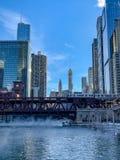 Opinião do retrato de um trem elevado 'do EL 'porque cruza o Chicago River que tem o vapor que aumenta acima das águas imagens de stock