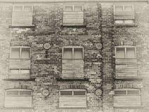 Opinião do Sepia de uma construção comercial abandonada velha do armazém com as paredes de tijolo resistidas e embarcada acima da imagens de stock