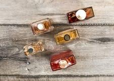 Opinião do Tabletop, garrafas coloridas das fragrâncias dos homens, no varrão de madeira fotografia de stock