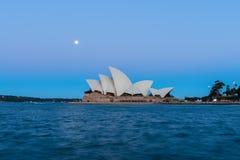 Opinião do teatro da ópera de Sydney com a Lua cheia no por do sol Fotos de Stock Royalty Free