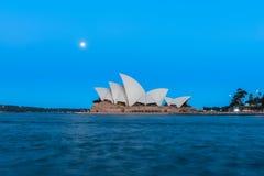 Opinião do teatro da ópera de Sydney com a Lua cheia no por do sol Foto de Stock