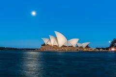 Opinião do teatro da ópera de Sydney com a Lua cheia no por do sol Imagem de Stock