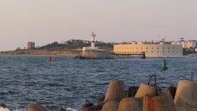 Opinião do tiro do lapso de tempo do farol branco no outro lado do litoral no por do sol vídeos de arquivo