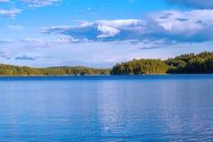 Opinião do verão do lago com reflexão das nuvens na água, Finlandia Imagem de Stock