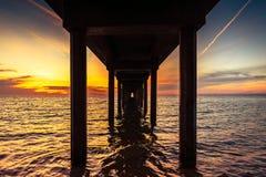 Opinião dramática do por do sol de debaixo de Brighton Jetty imagem de stock
