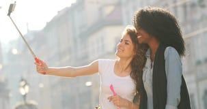 A opinião duas amigas de sorriso está tomando fotos de sua caminhada ao longo da rua Estão usando a vara do selfie filme