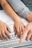 A opinião elevada os estudantes entrega o trabalho com um portátil Foto de Stock Royalty Free