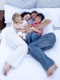 Opinião elevada os pais e as crianças que relaxam na cama Foto de Stock