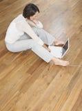 Opinião elevado a mulher que usa o portátil no revestimento de madeira imagem de stock