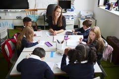 Opinião elevado o professor de escola primária fêmea que senta-se na tabela em uma sala de aula com alunos durante uma lição imagens de stock royalty free