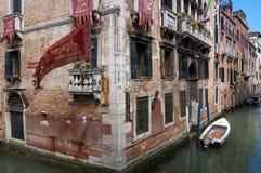Opinião estreita famosa do canal de Veneza com construções de tijolo, bandeiras com Foto de Stock