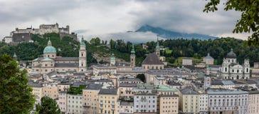 Opinião Façade da cidade de Salzburg e castelo medieval de Hohensalzburg com fundo nebuloso dos cumes e Forest Hills verde imagens de stock