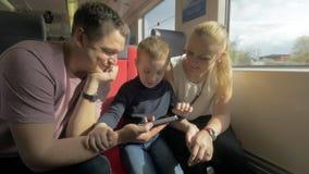 Opinião a família feliz na viagem railway usando o smartphone vídeos de arquivo