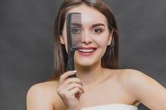 Opinião frontal uma moça bonita em uma lâmina branca Penteando o cabelo Sorriso, vista na câmera e guardar fotografia de stock royalty free