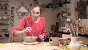 Opinião geral um ceramist da menina que alisa a superfície do potenciômetro de argila usando a borla na oficina da cerâmica video estoque
