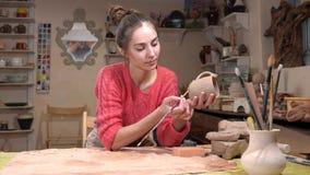 Opinião geral um ceramist da menina que seleciona uma borla apropriada para ajustar o copo cru da argila na oficina da cerâmica video estoque