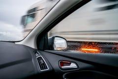 Opinião interior do veículo do espelho exterior que alcança um caminhão foto de stock
