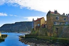 Opinião interna o porto e a Penny Nab de Staithes, perto de Scarborough, em North Yorkshire imagem de stock