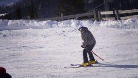 opinião 4k traseira o esquiador profissional que cinzela abaixo da inclinação nevado video estoque