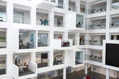 Opinião larga os estudantes em compartimentos do estudo na universidade moderna foto de stock